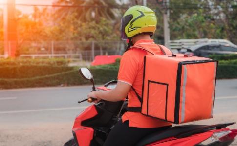 Motoboy em sua moto com mochila térmica